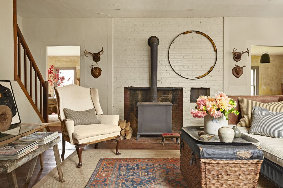 An old farmhouse living room with a fireplace has a red-orange and blue persian rug centered below traditional farmhouse furniture and decor, which includes an old wagon wheel hung on the wall above the fireplace, as well as some antlers. The brick surrounding the fireplace is painted white.