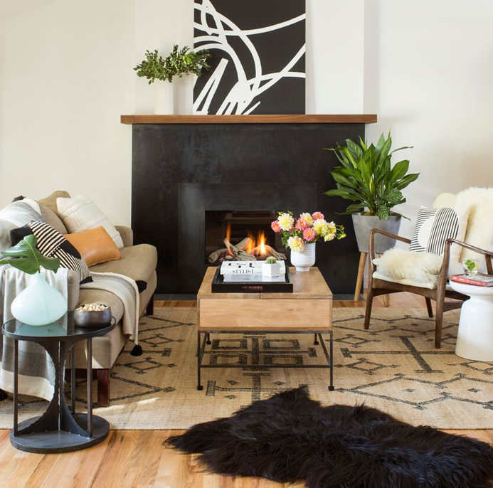 Cozy, boho living room with a medium black sheepskin pelt layered over the area rug: get the look on a budget